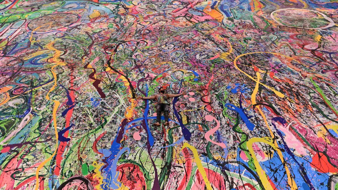 El artista británico contemporáneo Sacha Jafri se encuentra en su pintura récord titulada 'El viaje de la humanidad', en la ciudad emiratí de Dubai. - La pintura, que mide el tamaño de dos campos de fútbol, se puede ver en un hotel en Dubai, donde Jafri pasó meses encerrado debido a la pandemia de coronavirus.   Foto:GIUSEPPE CACACE / AFP
