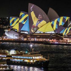 Los ferries pasan por la Ópera de Sídney iluminada por una proyección de la ex olímpica australiana Cathy Freeman para conmemorar el 20 aniversario de su victoria por la medalla de oro en el evento femenino de 400M en los Juegos Olímpicos de Sídney 2000, en Sídney. | Foto:DAVID GRAY / AFP