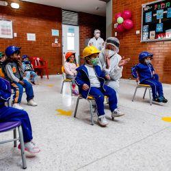 Niños con mascarilla participan en una clase durante la inauguración de los jardines de infancia en Bogotá, en medio de la pandemia del coronavirus COVID-19. | Foto:LEONARDO MUNOZ / AFP