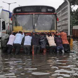 India, Mumbai: la gente empuja un autobús de transporte público en una calle que se inundó como consecuencia de las fuertes lluvias. | Foto:Ashish Vaishnav / DPA