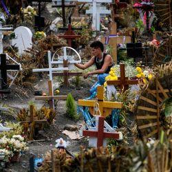 Un hombre visita una tumba en el Panteón Municipal en Valle de Chalco, estado de México, México, en medio de la pandemia del coronavirus COVID-19. | Foto:PEDRO PARDO / AFP