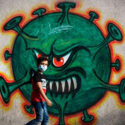 Un niño palestino pasa frente al arte callejero que muestra un coronavirus Covid-19, en la ciudad de Gaza. | Foto:MOHAMMED ABED / AFP