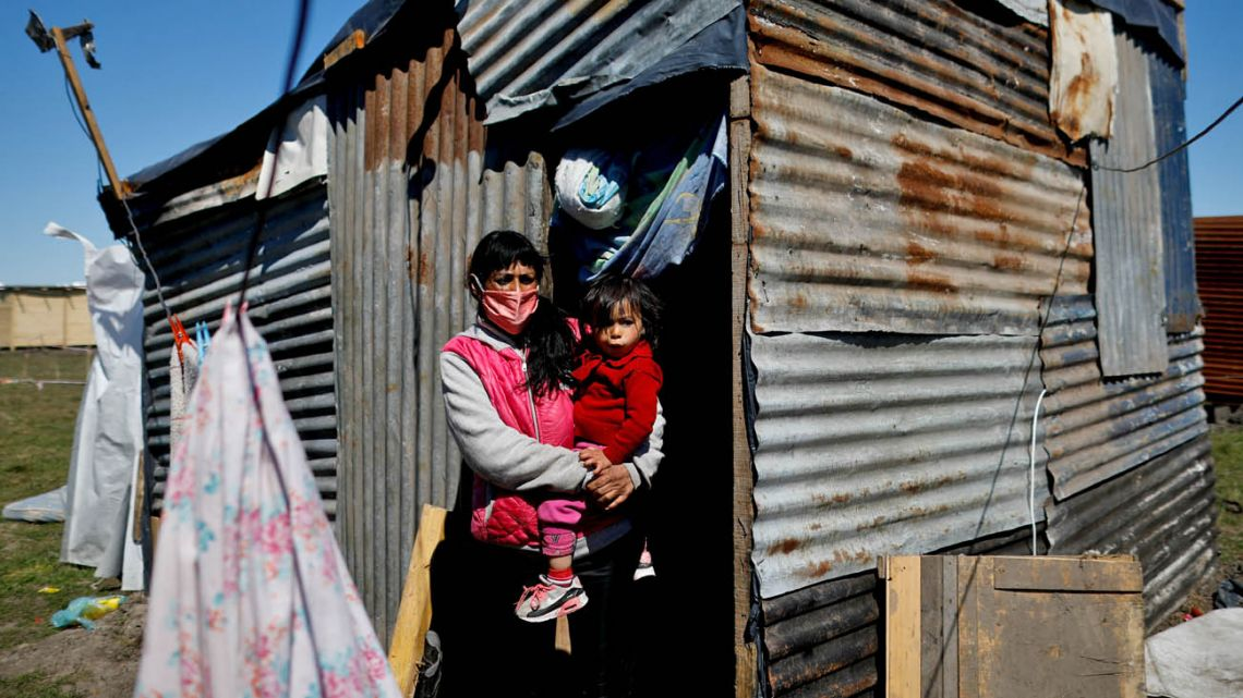 Cecilia Avila holds her daughter Triana, as she stands outside her makeshift home at the Guernica encampment.