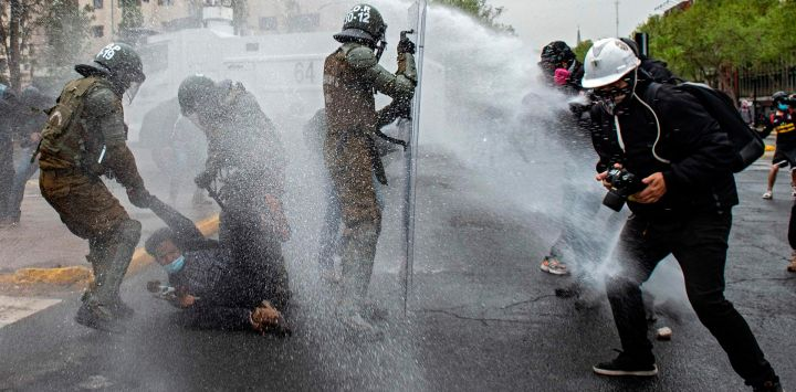 Un manifestante es arrestado por la policía antidisturbios durante un enfrentamiento tras una protesta contra el gobierno del presidente chileno Sebastián Piñera en Santiago, un mes antes de un referéndum que podría cambiar la Constitución del país.