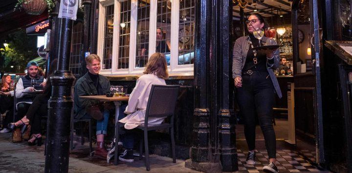 Una camarera lleva bebidas mientras la gente bebe afuera de un pub en Soho, en el centro de Londres.
