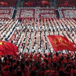 Esta foto muestra a estudiantes de primer año ondeando banderas chinas durante una ceremonia de graduación en la Universidad de Wuhan en Wuhan, en la provincia central china de Hubei. | Foto:STR / AFP