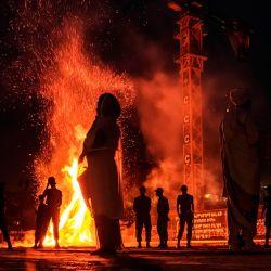 La gente se para frente a una hoguera durante la celebración de la víspera de la festividad ortodoxa etíope de Meskel, que conmemora el descubrimiento en el siglo IV de la Cruz Verdadera por la emperatriz romana Helena, en Addis Abeba. | Foto:EDUARDO SOTERAS / AFP