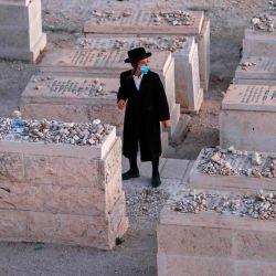 Un judío ultraortodoxo reza en un cementerio en el Monte de los Olivos en Jerusalén oriental. | Foto:AHMAD GHARABLI / AFP