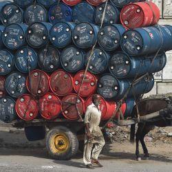 Un hombre parado junto a un carro de caballos cargado de bidones de aceite en una calle de Lahore. | Foto:Arif Ali / AFP