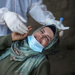 Territorios Palestinos, Deir Al-Balah: un médico palestino del Comité de Control de Infecciones en Deir al-Balah recolecta un hisopo nasal de una mujer durante una campaña de pruebas de coronavirus. | Foto:Mahmoud Khattab/ DPA