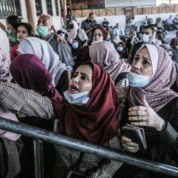 Los palestinos, enmascarados debido a la pandemia del coronavirus COVID-19, esperan cruzar al lado egipcio del cruce fronterizo de Rafah en el sur de la Franja de Gaza. | Foto:SAID KHATIB / AFP