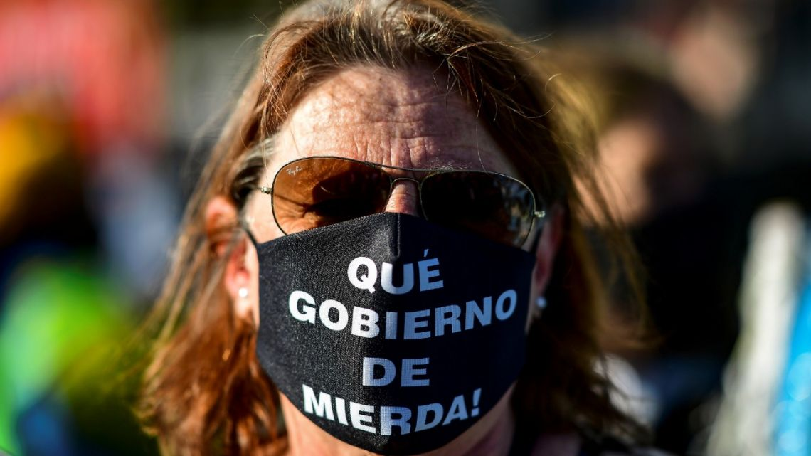 """In this photo taken on August 17, 2020, a woman wears a face mask reading """"What a shitty government!"""" during a protest against the government's health policies in Buenos Aires."""