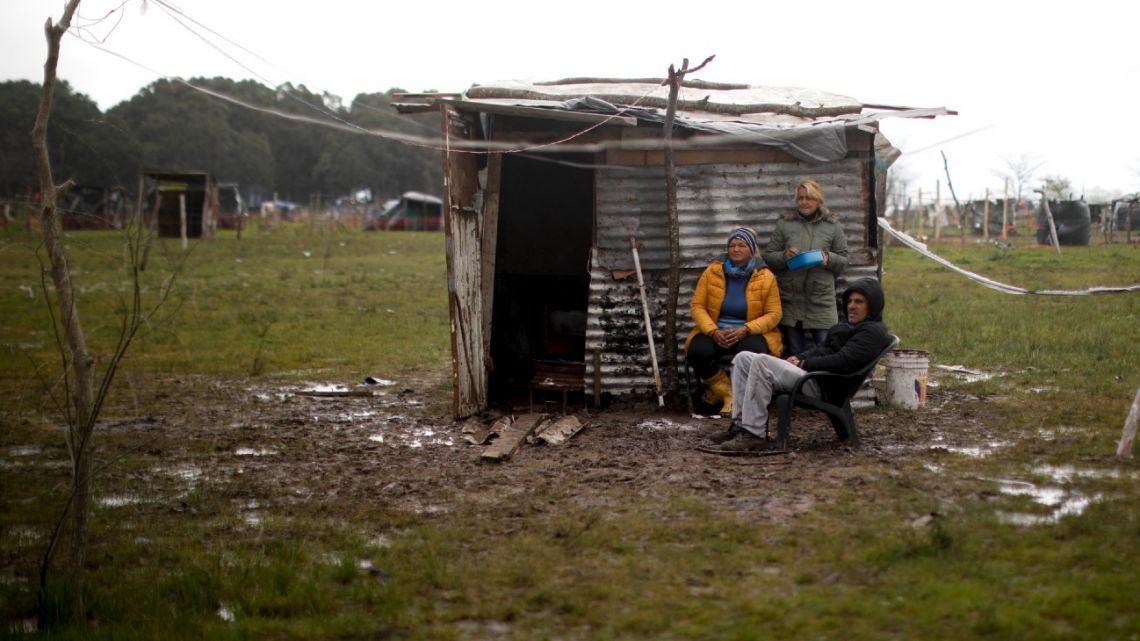 A family sits outside a makeshift home at a squatters camp in Guernica, Buenos Aires Province.