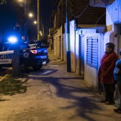 Neighbors watch as members of the Federal Police pull cars over at a checkpoint in 'La Granada,' a violent neighbourhood in Rosario.