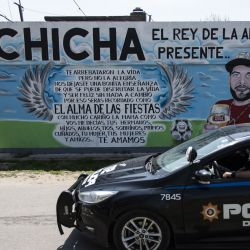 A police car drives past a mural depicting 'Chicha,' a victim of violence, at the neighbourhood of 'Las Flores,' in Rosario.