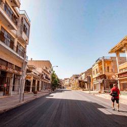 Un periodista pasa junto a edificios abandonados a lo largo de una calle de Varosha, en la zona vallada de Famagusta, en el norte ocupado por los turcos de la dividida isla de Chipre en el este del Mediterráneo.   Foto:Birol Bebek / AFP