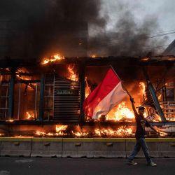 Indonesia, Yakarta: un manifestante ondea la bandera de Indonesia mientras pasa junto a una propiedad en llamas durante una manifestación contra un proyecto de ley general del gobierno sobre creación de empleo que, según creen, privará a los trabajadores de sus derechos. | Foto:Donal Husni / ZUMA Wire / DPA