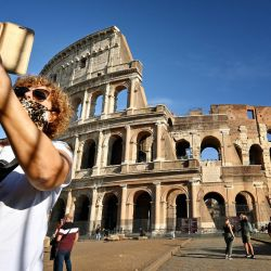Una mujer que lleva una máscara facial se toma una 'selfie' mientras se para frente al Coliseo en Roma.- El gobierno de Italia ha obligado a usar protección facial al aire libre, en un intento de contrarrestar la propagación del coronavirus. Pandemia de COVID-19. | Foto:Alberto Pizzoli / AFP