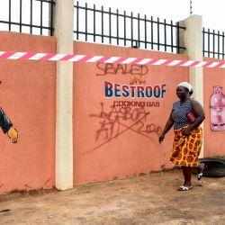La gente camina por las cercas de los depósitos de gas después de la explosión de un camión de gas, dejando cinco muertos y varios más heridos en el distrito Baruwa-Ipaja de Lagos.   Foto:PIUS UTOMI EKPEI / AFP