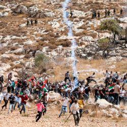 Los manifestantes palestinos corren en medio del humo de los gases lacrimógenos durante los enfrentamientos con las fuerzas de seguridad israelíes tras una manifestación contra la expansión de los asentamientos, cerca de la aldea de Beit Dajan, al este de Nablus. | Foto:JAAFAR ASHTIYEH / AFP
