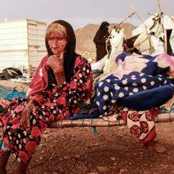 Una anciana observa sentada en una cama improvisada mientras la gente intenta rescatar las tiendas de campaña dañadas por las lluvias torrenciales en un campamento para yemeníes desplazados por el conflicto en la provincia norteña de Hajjah. | Foto:ESSA AHMED / AFP