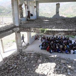 Los alumnos yemeníes asisten a clase el primer día del nuevo año académico, en un aula improvisada en el recinto escolar que sufrió graves daños hace dos años en un ataque aéreo, en la tercera ciudad del país, Taez.   Foto:AHMAD AL-BASHA / AFP