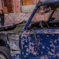Los residentes locales se paran en una calle cerca de un automóvil dañado después de que fue alcanzado por un misil en Gandja, Azerbaiyán, cerca de la disputada capital de la provincia de Nagorno-Karabaj, Stepanakert, mientras los combates entre las fuerzas armenias y azerbaiyanas se extendían antes de una primera. encuentro de mediadores internacionales en Ginebra. | Foto:Bulent Kilic / AFP
