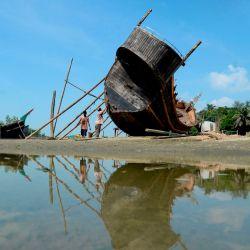 Los trabajadores reparan el casco de un barco de pesca en una playa en Cox's Bazar. | Foto:Munir Uz zaman / AFP