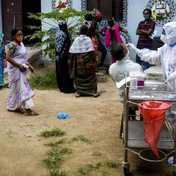 Un trabajador de salud recolecta una muestra de hisopo de un hombre para realizar una prueba del coronavirus Covid-19 en un centro de salud comunitario en las afueras de Hyderabad. | Foto:Noah Seelam / AFP