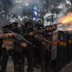 La policía antidisturbios lanza gases lacrimógenos para dispersar a los manifestantes estudiantiles durante el segundo día de una huelga de tres días de trabajadores contra un proyecto de ley general del gobierno sobre creación de empleo que creen que privará a los trabajadores de sus derechos, en Bandung. | Foto:TIMUR MATAHARI / AFP