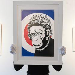 Inglaterra, Londres: la asistente de la galería Sophia Shim sostiene una impresión de edición limitada de Monkey Queen (2003) de Banksy. | Foto:Kirsty O'connor / PA Wire /DPA