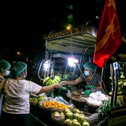 La gente compra verduras en una tienda ambulante móvil en Yangon. | Foto:Sai Aung Main / AFP