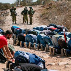 Los soldados israelíes se quedan esperando mientras los manifestantes palestinos realizan las oraciones musulmanas del viernes durante una manifestación contra los asentamientos judíos en la ciudad de Asira Shamaliya en la ocupada Cisjordania cerca de Nablus. | Foto:Abbas Momani / AFP