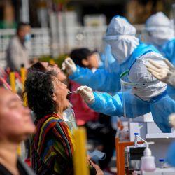Un trabajador de la salud toma un hisopo de un residente para ser examinado por el coronavirus COVID-19 en Qingdao, en la provincia oriental de Shandong. | Foto:STR / AFP