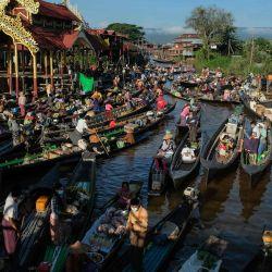 La gente compra productos a los vendedores en un mercado flotante que se celebra en barcos en el lago Inle en el estado de Shan de Myanmar. | Foto:Wai Min Phyoe / AFP