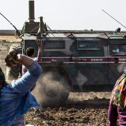 Sirios arrojan piedras a un convoy militar ruso cerca de la aldea de Ein Diwar en la provincia nororiental de Hasakeh, en Siria. | Foto:Delil Souleiman / AFP