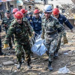 Los equipos de rescate se llevan el cuerpo de una víctima en el lugar de la explosión alcanzado por un cohete durante los combates entre Armenia y Azerbaiyán sobre la región separatista de Nagorno-Karabaj, en la ciudad de Ganja, Azerbaiyán. | Foto:Bulent Kilic / AFP