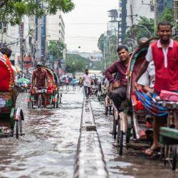 Bangladesh, Dhaka: los viajeros y los peatones se quedan atascados después de que la Ruta Verde de Dhaka quedara anegada debido a las fuertes lluvias. | Foto:Nayan Kar / DPA