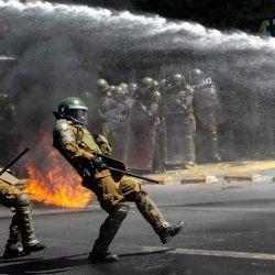 Un cóctel molotov estalla frente a la policía antidisturbios durante una protesta en el marco del Día de la Carrera, en el centro de Santiago. | Foto:Martin Bernetti / AFP