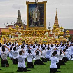 Los estudiantes presentan sus respetos ante el retrato del difunto rey tailandés Bhumibol Adulyadej, durante la ceremonia oficial que marca el cuarto aniversario de su muerte, frente al Gran Palacio de Bangkok. | Foto:Lillian Suwanrumpha / AFP