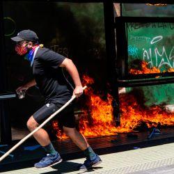 Un manifestante corre durante los enfrentamientos con la policía antidisturbios que estallaron durante una protesta en el marco del Día de la Carrera, en el centro de Santiago. | Foto:Martín Bernetti / AFP