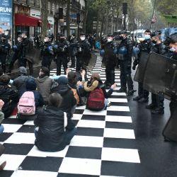Activistas del grupo de protesta ambiental Extinction Rebellion se sientan en el suelo entregados por gendarmes franceses en una calle de París, como parte de una semana de acciones del grupo. | Foto:STEPHANE DE SAKUTIN / AFP
