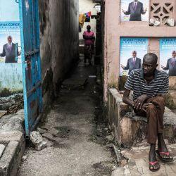 Un hombre se sienta frente a los carteles de campaña del presidente Alpha Conde en Conakry. - El presidente aspira a un tercer mandato con las elecciones presidenciales que se celebrarán el 18 de octubre de 2020, desafiando a los críticos que dicen que este año se vio obligado a aprobar una nueva constitución que le permitió eludir los límites presidenciales de dos mandatos. | Foto:JOHN WESSELS / AFP