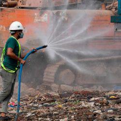 Un empleado de la zona norte de la Corporación Municipal de Delhi rocía agua para controlar el polvo en el vertedero de Bhalswa en Nueva Delhi. | Foto:Prakash Singh / AFP