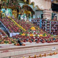 Un sacerdote hindú reza frente a ofrendas de frutas, que se distribuirán entre los pacientes con coronavirus Covid-19, con motivo del Festival hindú 'Ekadasi' en el templo Swaminarayan Gurukul Memnagar en Ahmedabad. | Foto:SAM PANTHAKY / AFP