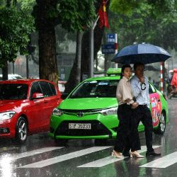 Los peatones cruzan una calle durante las fuertes lluvias en Hanoi cuando la tormenta tropical Nangka tocó tierra en el centro-norte de Vietnam. | Foto:Manan Vatsyayana / AFP