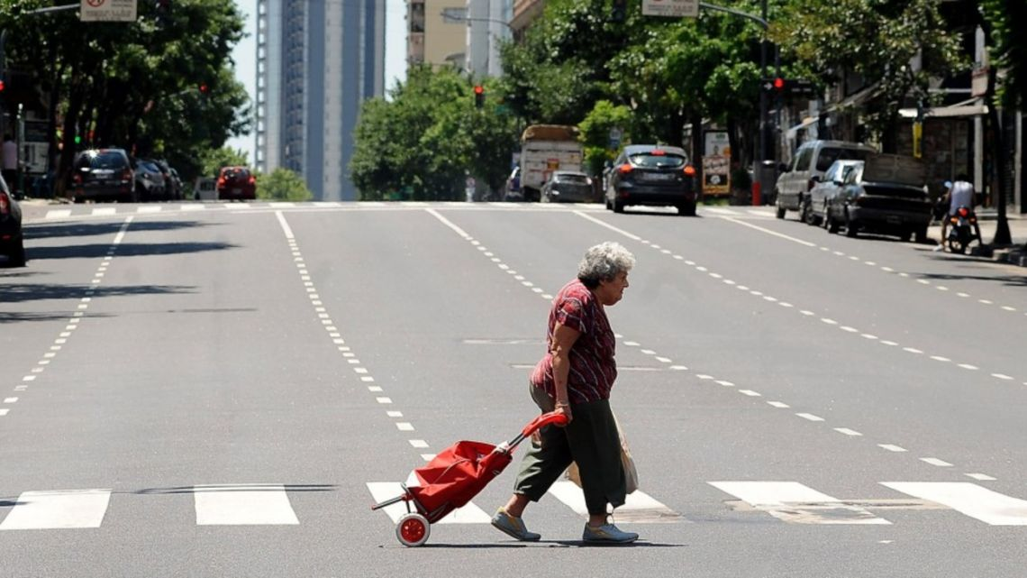 A woman pulls her shopping trolley through empty streets, during the coronavirus lockdown in Buenos Aires.
