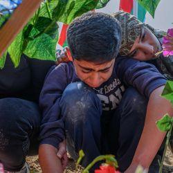 Los familiares de un soldado de 29 años muerto durante los enfrentamientos con Armenia, lloran mientras se agacha junto a su tumba, cerca de la ciudad de Agdam, durante el conflicto militar en la región separatista de Nagorno-Karabaj.   Foto:Bulent Kilic / AFP