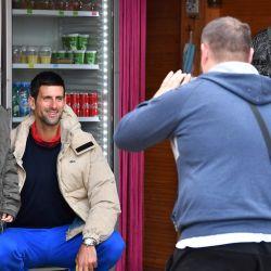 El jugador de tenis número 1 del mundo, Novak Djokovic se toma un momento para ser fotografiado con un joven fan, cuando llega al parque arqueológico    Foto:ELVIS BARUKCIC / AFP