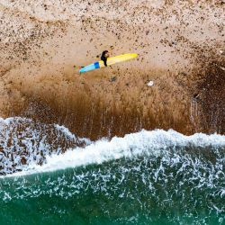 Esta imagen de vista aérea muestra a un surfista sosteniendo su tabla de surf después de terminar una sesión de surf en Klitmoller, Dinamarca.   Foto:Jonathan Nackstrand / AFP